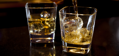 Whiskey poured into two glasses on bar
