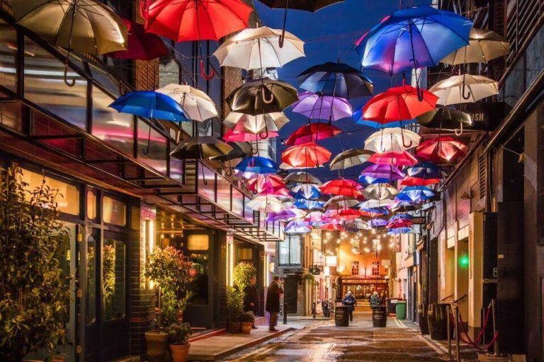 A street with umbrellas hanging above at night.