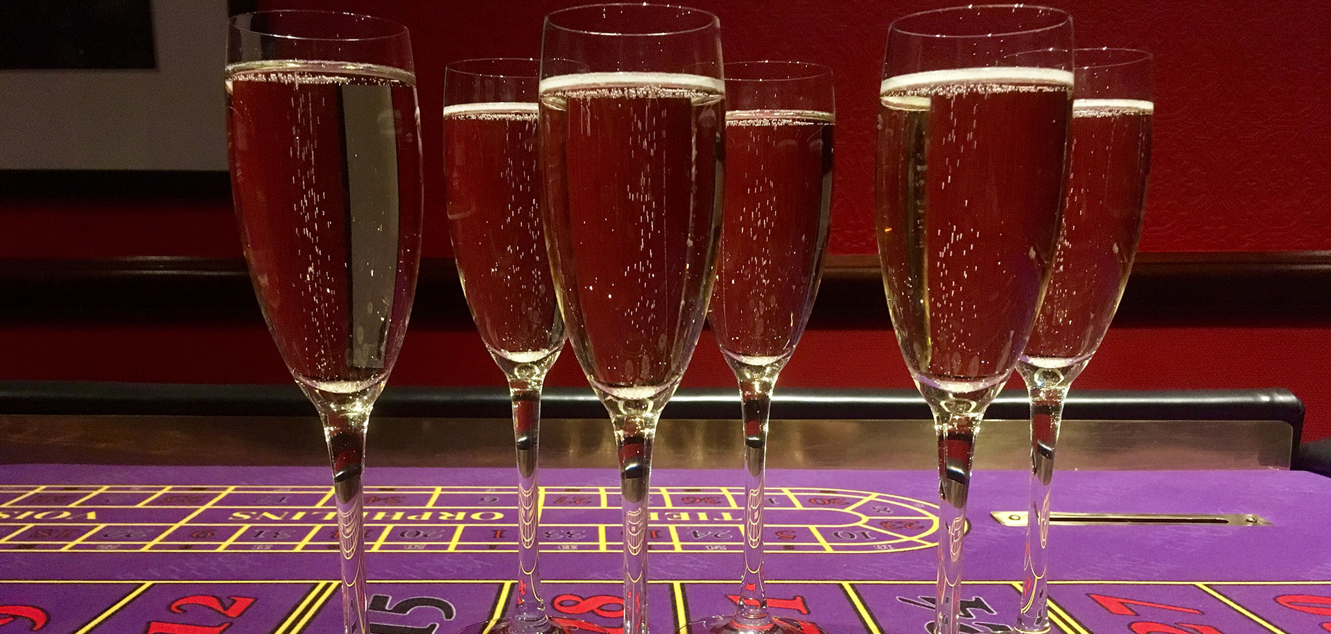 A few glasses of bubbly on a blackjack table.