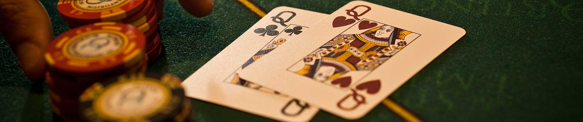 Hands reaching for Poker chips on green background