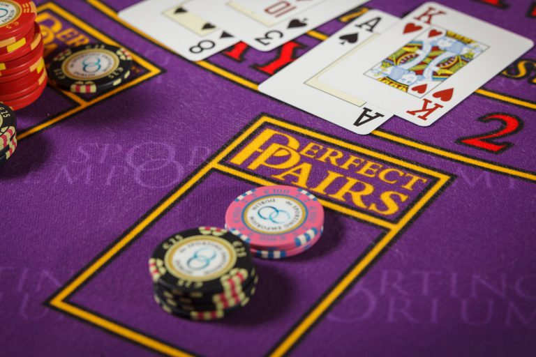 "Casino chips and cards on a purple table with a sign ""Perfect Pairs""."