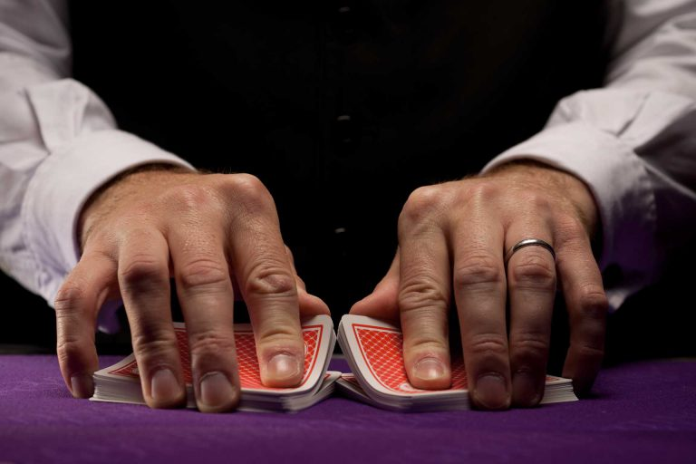 A poker dealer shuffling cards on a table